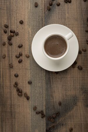 Coffee in a white cup and coffee beans on the table. Top view. Dark background. Banco de Imagens