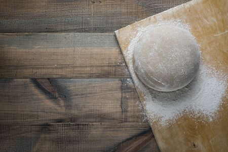 Risen or proofed yeast dough for bread or pizza on a floured slate surface. Top view
