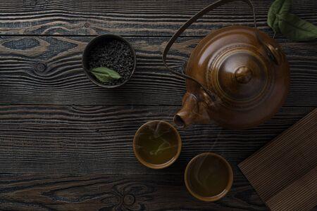 Tea concept. Teapot with tea on table.. Asian tea bowl and teapot.
