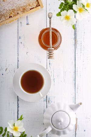 Honey in a glass jar, a wooden spoon for honey, honeycombs, tea in a white cup and rose hips on a wooden table. Top view. Archivio Fotografico