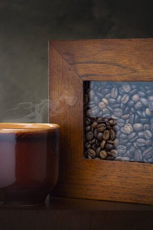 Cup of coffee and coffee beans on the table. Dark background. Archivio Fotografico