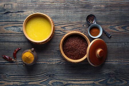 Ghee or clarified butter in ceramic bowls and red rice with different spices on an old wooden table. Top view. Stock Photo