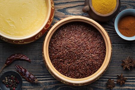 Ghee or clarified butter in ceramic bowls and red rice with different spices on an old wooden table. Top view.