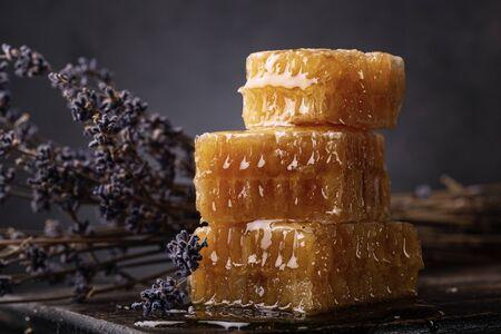Honey background. Sweet honey comb and lavender close-up. Dark background. Archivio Fotografico