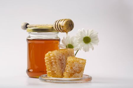 Honey background. Sweet honey in the comb. Fresh honey in a glass jar, honeycombs, honey spoon and white flowers on a light background.