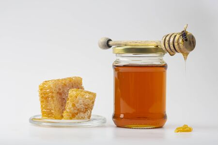 Honey background. Sweet honey in the comb. Fresh honey in a glass jar, honeycombs, a spoon for honey and a bee on a light background.