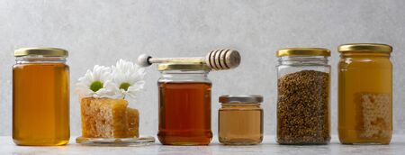 Honey background. Sweet honey in the comb. A variety of honey in glass jars and honey honeycombs on the table. Banner.
