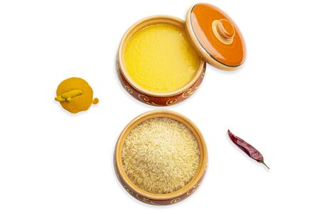 Homemade ghee, rice in a ceramic pot, red peppers and turmeric spices. Isolated white background. Top view.  Ayurveda