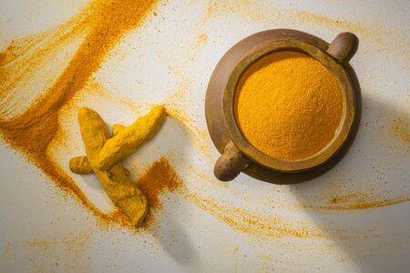 Turmeric powder and turmeric on white background, indian spice,healthy seasoning ingredient for vegan cuisine concept. Top view