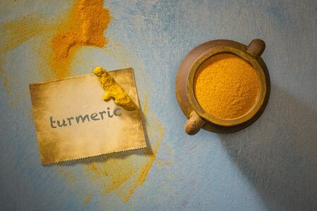 Turmeric powder and turmeric and label with the inscription, indian spice,healthy seasoning ingredient for vegan cuisine concept. Top view Archivio Fotografico