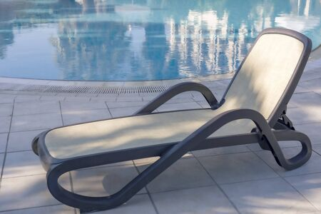 A deck chair next to a blue water pool. Warm sunny day. Summer holidays.