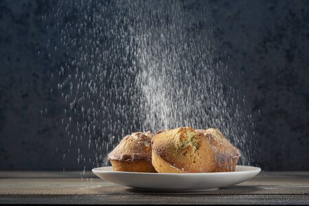 Homemade fresh muffins sprinkled with powdered sugar in a white ceramic plate. Dark background.