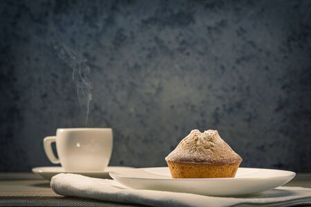 Homemade fresh muffins sprinkled with icing sugar and fresh coffee on a white table. Tasty and healthy breakfast.