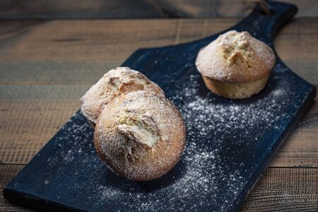 Homemade fresh muffins sprinkled with icing sugar on a wooden board. Dark background.