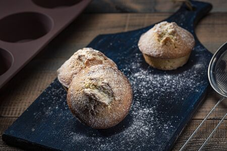 Homemade fresh muffins sprinkled with icing sugar and baking dish on a wooden table. Dark background.