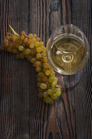 White wine in a glass and grapes on an old wooden table. Top view.