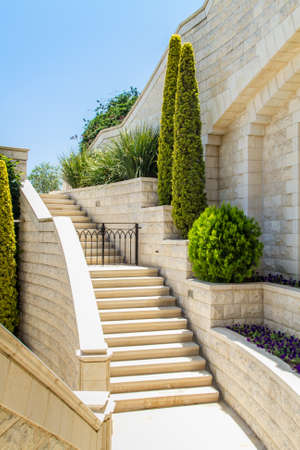 landscaped garden: Mediterranean landscaped garden with a stone staircase. Trimmed trees and bushes near a white wall