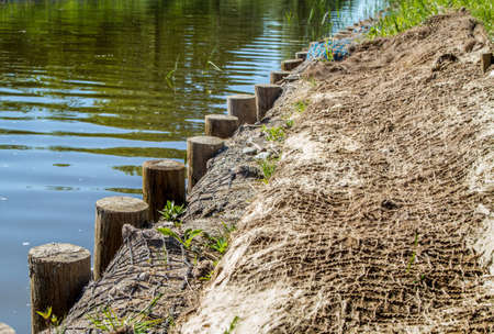 strengthening: Strengthening shore line with wooden piles and net. Elblag Canal, Poland Stock Photo