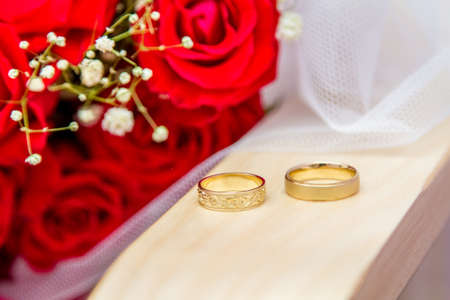 chuppah: Jewish wedding - Wedding rings of bride and groom near a bouquet of red roses. Close-up