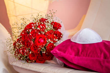 chuppah: Jewish wedding - Kippah of groom and bouquet with red roses of bride Stock Photo
