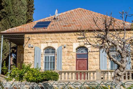 paisaje mediterraneo: Mediterráneo paisaje urbano - Casa de piedra con techo de tejas y ventanas de arco con persianas, frente a la piedra blanca en Jerusalén, Israel