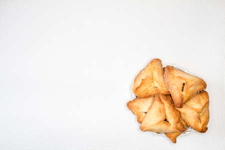 hamantaschen: Hamantaschen or Hamans ears - triangular cookies for Jewish holiday of Purim, on light background Stock Photo