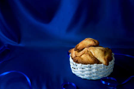 book of esther: Hamantaschen or Hamans ears - triangular cookies for Jewish holiday of Purim on dark blue silk background Stock Photo