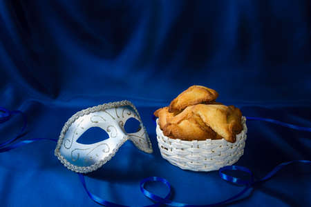 book of esther: Jewish holiday of Purim. Hamantaschen cookies and carnival mask on dark blue silk background