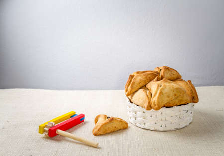 book of esther: Jewish holiday of Purim. Hamantaschen cookies,  and wooden gragger, free space for text Stock Photo