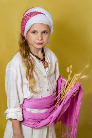 the great grandmother: Girl in the image of Ruth the Moabitess holds heads of grain, card for Jewish holiday of Shavuot