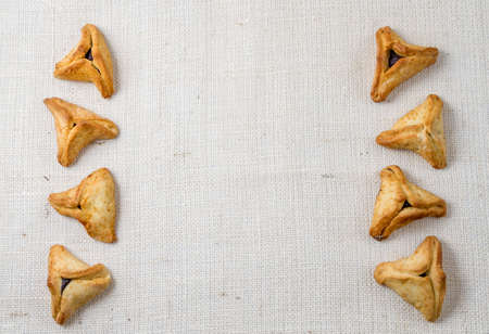 book of esther: Jewish holiday of Purim. Hamantaschen cookies on canvas background with free space for text