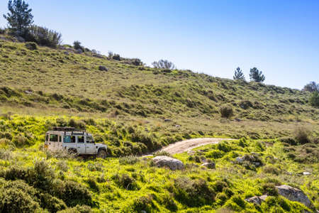 shalom: SUV rides on the country road among hills and meadows in Neve Shalom, Israel