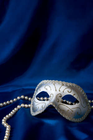 book of esther: Silver carnival mask and pearl on dark blue silk background Stock Photo