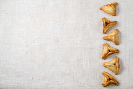 book of esther: Jewish holiday of Purim. Hamantaschen cookies on canvas background Stock Photo
