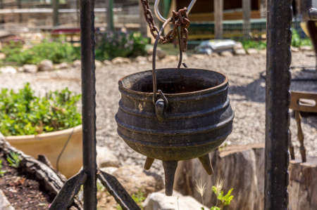 Old cast iron pot on a three legs for cooking is suspended on the hook, on the farm in the desert, Israel