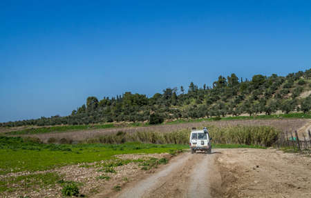 shalom: SUV rides on the country road among meadows in Neve Shalom, Israel