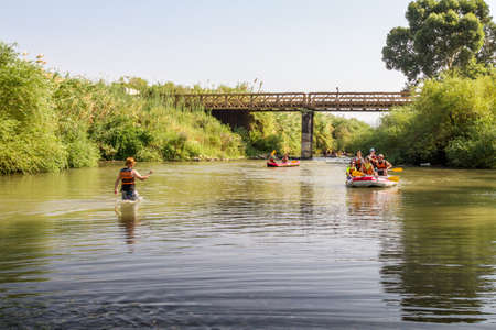 paddles: JORDAN RIVER, ISRAEL - OCTOBER 2: Group of teenagers rafting on the Jordan River in Israel on October 2, 2015