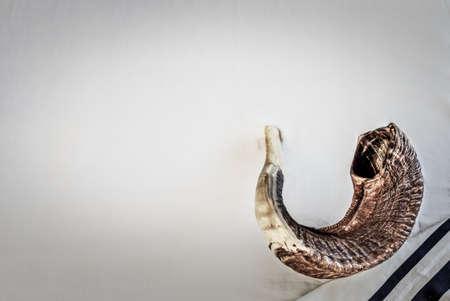 Shofar on a tallit - ancient musical trumpet made of rams horn on Jewish prayer shawl