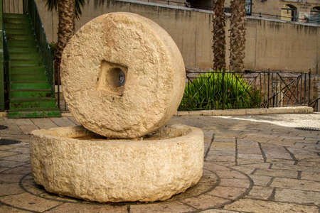 squeeze shape: Ancient millstone for olive oil press in the ancient Roman main street - Cardo in Jewish Quarter in Old City of Jerusalem, Israel
