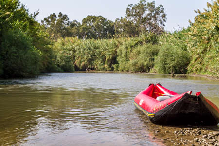 river rafting: Red inflatable boat in shallow water on the bank of the Jordan River, Israel