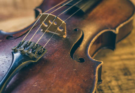 Old violin on a wooden background, stringed musical instrument in close-up