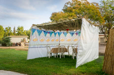 Jewish Holiday Sukkot. The sukkah - symbolic temporary hut, fabric sukkah with table and chairs, top covered with palm branches Stock Photo