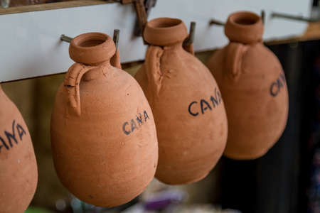 The pottery jugs, small souvenirs imitating ancient wine jugs in the gift shop in Cana of Galilee, Israel. Selective focus