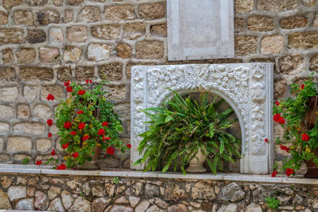 Bas-relief with floral ornament and flowers in pots adorns the courtyard of the Cana Greek Orthodox Wedding Church in Cana of Galilee, Kfar Kana, Israel.
