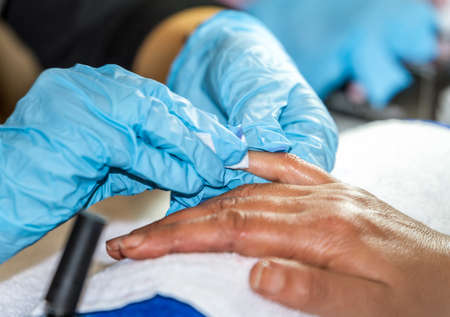 Manicure process in beauty salon, care of hands, close up