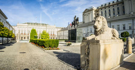 WARSAW, POLAND - SEPTEMBER 17: Stone statue of a lion lying in front of the Presidential Palace, behind it is a monument to Prince Jozef Poniatowski in Warsaw, Poland on September 17, 2016 Editorial