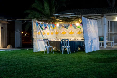 sukkoth festival: Fabric sukkah decorated with printed pattern and hebrew text of blessing: Grant peace everywhere goodness and blessing, Grace, lovingkindness and mercy to us and unto all Israel, Your people. Night