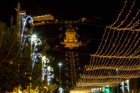 Christmas decorations and lighting on the street at evening, view of the Bahai gardens from Sderot Ben Gurion in Haifa, Israel