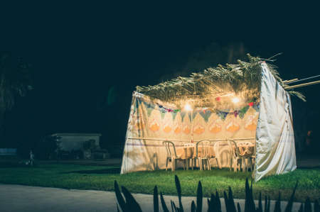 Fabric sukkah decorated with printed pattern and hebrew text of blessing: Grant peace everywhere goodness and blessing, Grace, lovingkindness and mercy to us and unto all Israel, Your people. Night, toned image