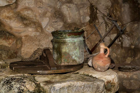 holy jug: The Old iron bucket and the clay jug on the ancient stone water well in Nazareth Village, Israel. Ancient Holy Land